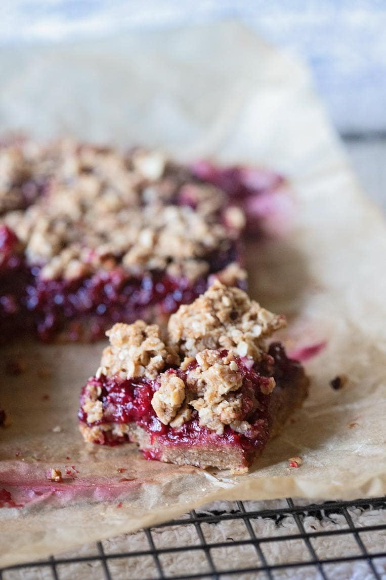 a cut healthier raspberry crumble bar on parchment paper