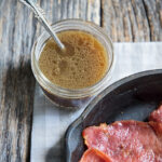 red eye gravy in a jar with a spoon ready for country ham in a skillet