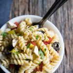 rotini pasta salad with mozzarella and tomato in a bowl with a spoon