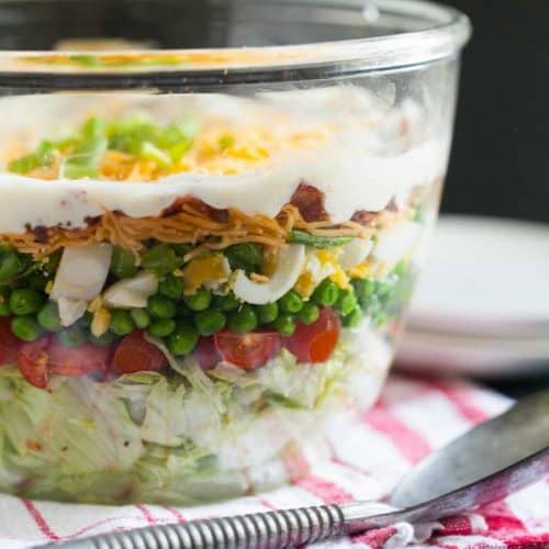 Seven layer salad in a clear bowl on a plaid napkin.