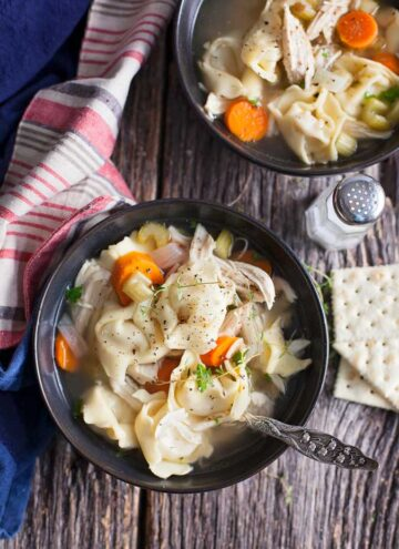 chicken tortellini soup in bowls on a table