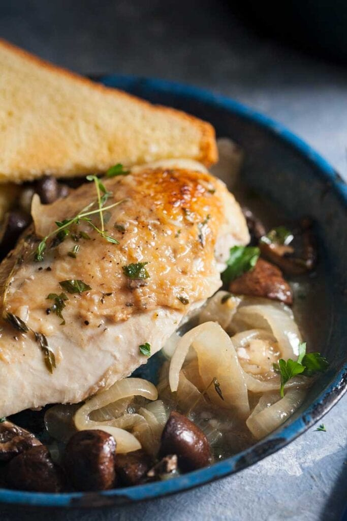 a plate of chicken and mushrooms with toast on a plate
