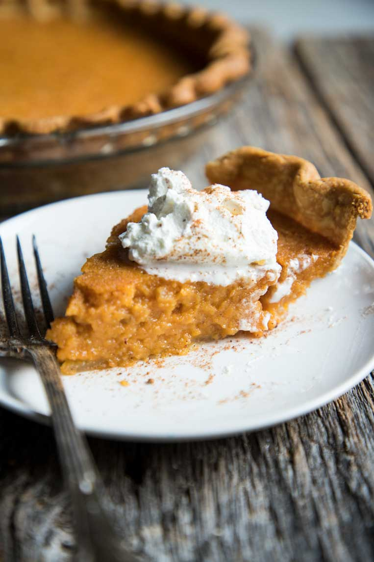 a slice of southern sweet potato pie on a plate with whipped cream and cinnamon
