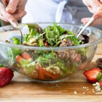 a bowl of steak salad being tossed together with two forks