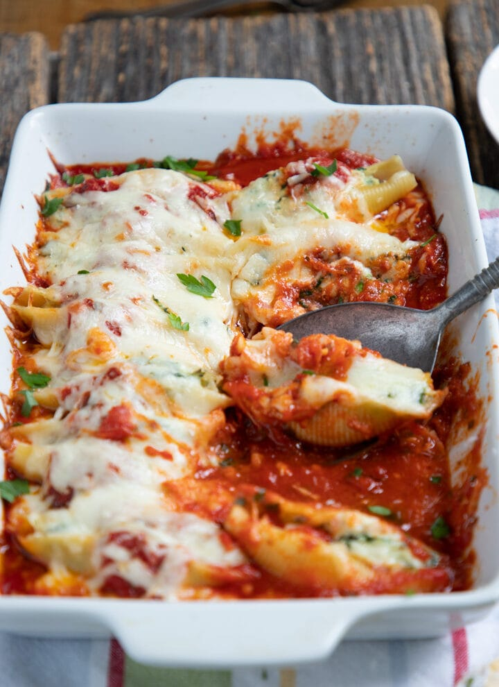 9x13 pan of stuffed shells with spinach on a wooden table.