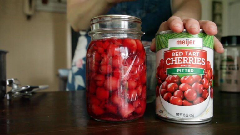 two cans of cherries on a table; one store bought and one home canned
