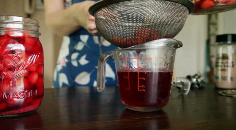 a measuring cup with cherry liquid from the can being poured in