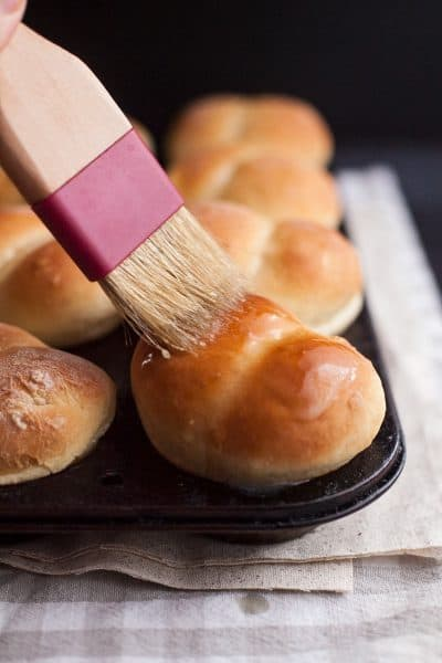 brush spreading warm butter over dinner rolls in a muffin tin